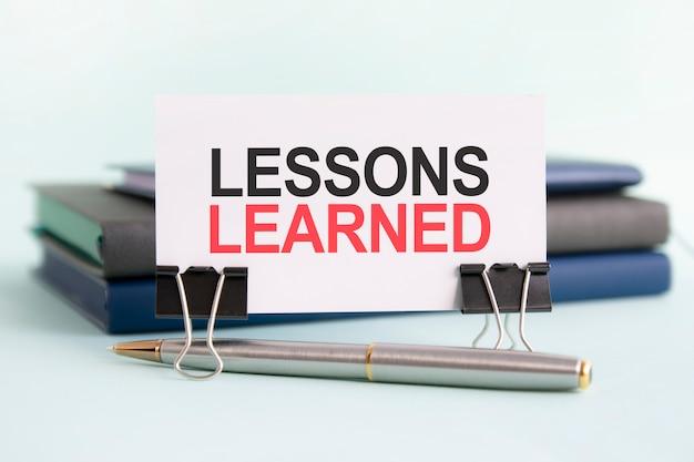 本の背景にテーブルの上の紙のクリップの上に、テキストの教訓を学んだ白いカードが立っています。セレクティブフォーカス