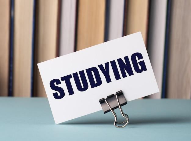 本の背景にテーブルの上の紙のクリップの上に「studying」というテキストが書かれた白いカードが立っています。焦点ぼけ