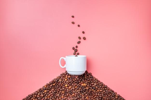 Белая керамическая чашка стоит на холме из кофейных зерен