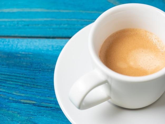 完全なエスプレッソと白いコーヒーマグは、受け皿と青い木製の背景に設定されています。コーヒー、エナジードリンク。おいしい泡