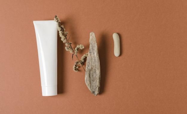 白い化粧品のチューブは、自然な装飾が施された茶色の背景にあります