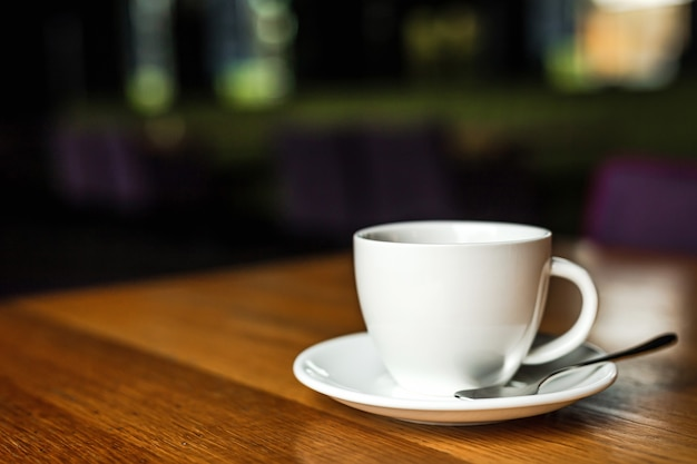Белая чашка черного кофе, белое блюдце, ложка, деревянный стол в кафе