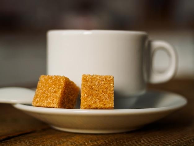 白いカップのコーヒーと2つの黄砂糖。