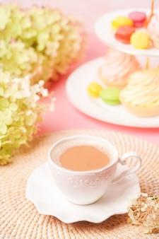 Белая чашка кофе со сладостями и букет цветов в мягких пастельных тонах. поздравления с днем рождения или с днем матери. закрыть вверх