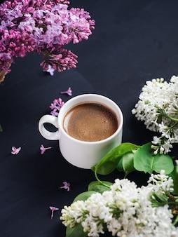 Белая чашка ароматного кофе на темном каменном столе с ветвями пурпурной и белой сирени. весеннее утро и настроение