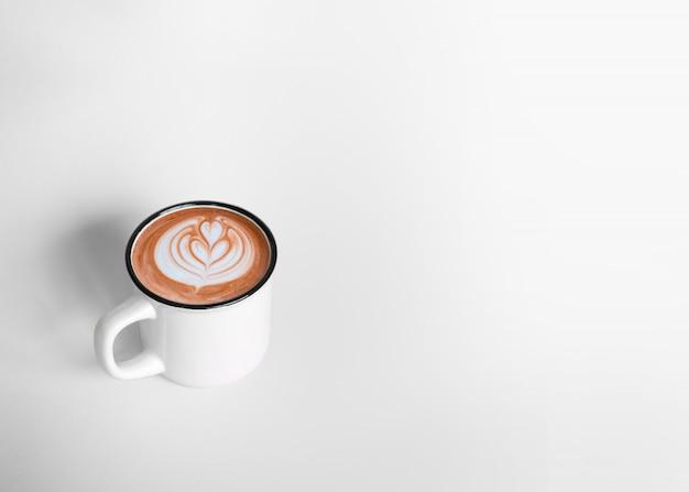 コピースペースと白い背景の上のホットコーヒーカフェラテアートの白いカップ。上面図