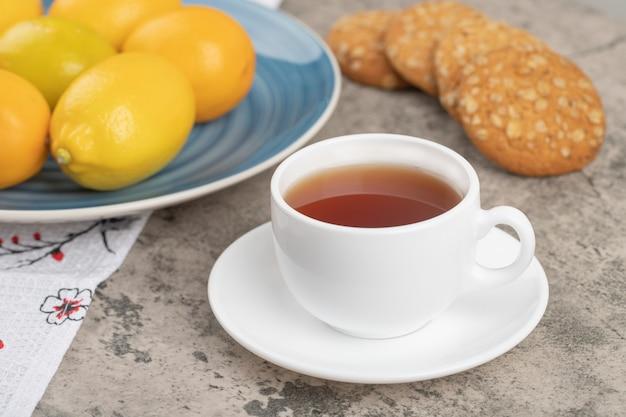 Белая чашка горячего чая с овсяным печеньем на скатерти.