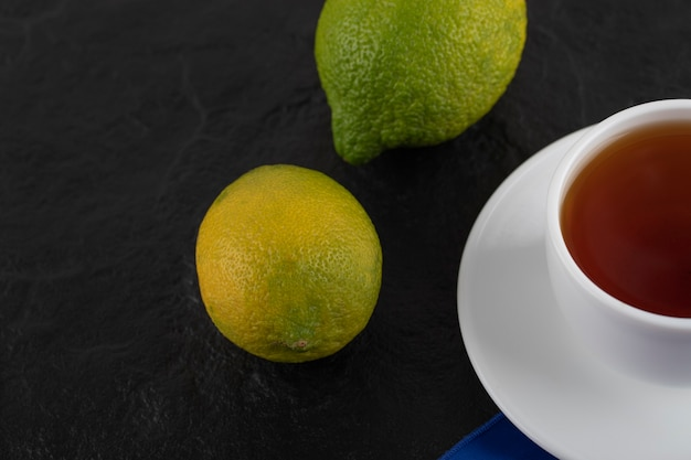 2つのグリーンレモンと熱いお茶の白いカップ。