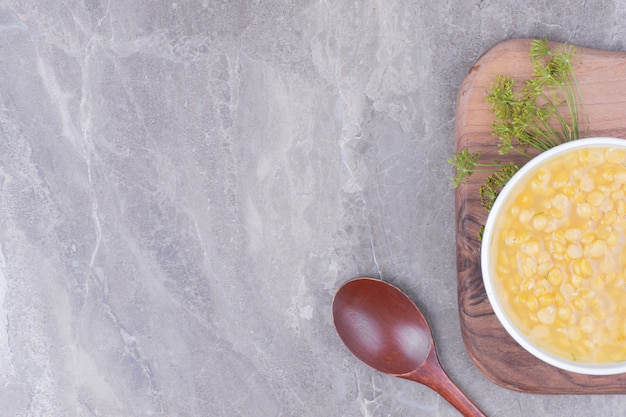 木製の大皿にエンドウ豆のスープの白いカップ