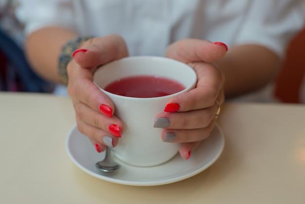 Белая чашка чая в руках девушки