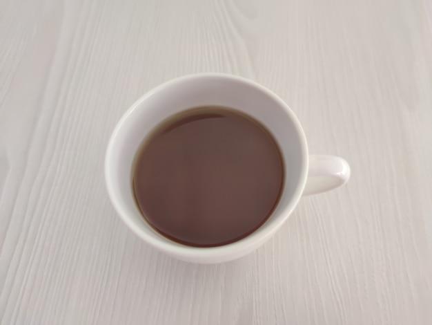 Белая чашка чая или кофе и блюдце на деревянном столе с копией пространства. фотография для меню кафе или ресторана или фона упаковки.