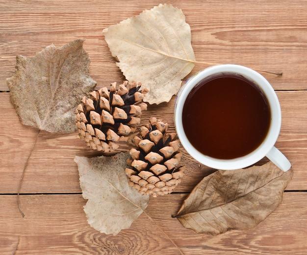 お茶、松ぼっくり、木製のテーブルの落ち葉の白いカップ。秋冬の静物。