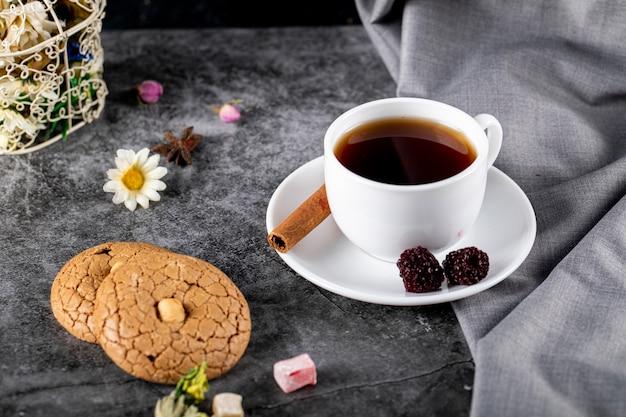 Белая чашка чая с ягодами, корицей и печеньем