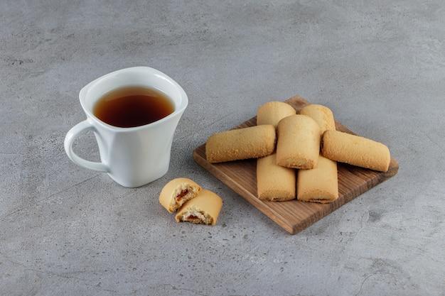 Белая чашка чая со сладким свежим печеньем в деревянной доске на камне.