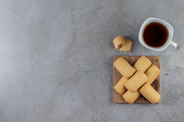 石の上の木の板に甘い新鮮なクッキーとお茶の白いカップ。
