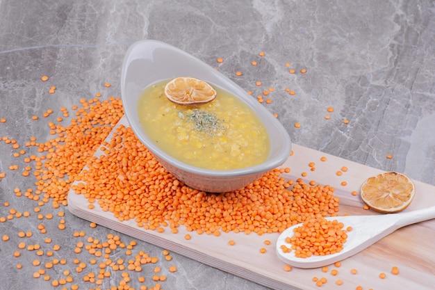 赤いレンズ豆が周りにある木製の大皿に黄色いエンドウ豆のスープの白いカップ。