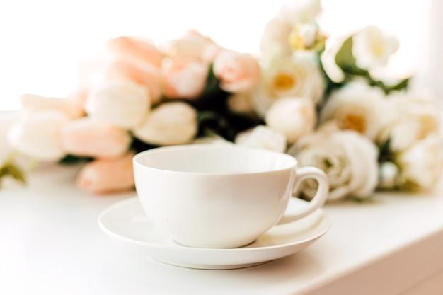 접시에 있는 흰색 컵은 흰색 튤립 배경에 서 있다