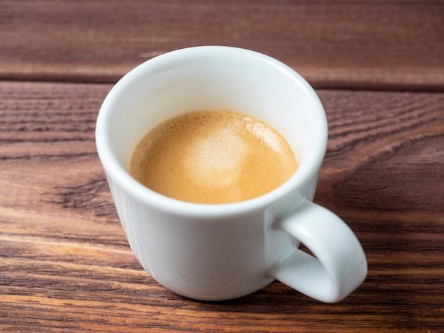 木製の背景に美味しくて香り高いエスプレッソが入った白いカップ。側面図