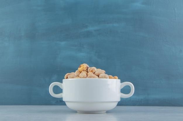 맛있는 말린 과일이 가득한 흰색 깊은 컵.