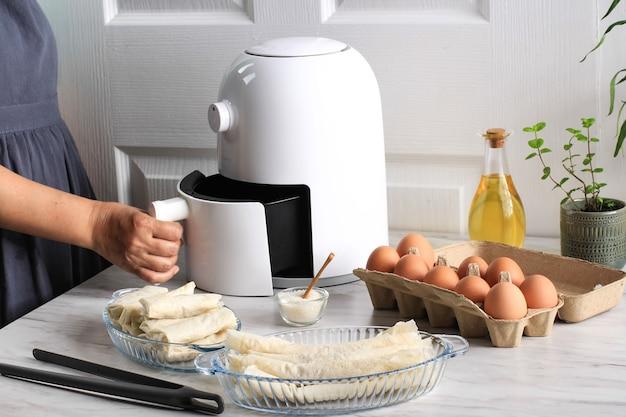 냄비에 작은 식물이 있는 주방의 나무 테이블에 흰색 튀김기 또는 오일 프리 프라이어 기기, 집게, 투명 베이킹 접시 및 계란 트레이가 있습니다(에어 프라이어)