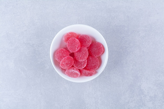 灰色の表面に赤い砂糖のようなフルーツゼリーキャンディーでいっぱいの白い深いプレート