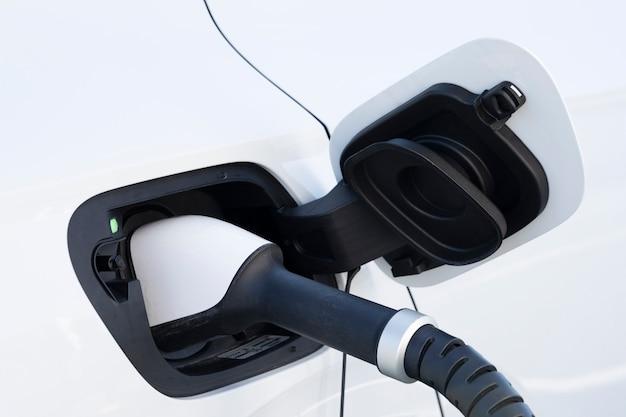 Зарядка белого электромобиля на станции