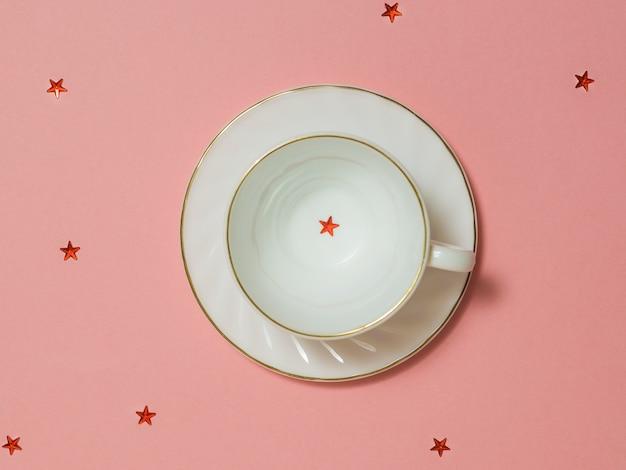 ピンクの背景に赤い星と白い空のコーヒーカップ。ホットドリンクの料理。