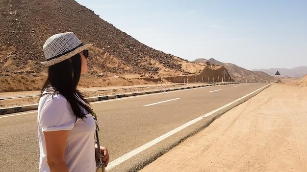 Белая девушка в шляпе стоит у широкой пустынной асфальтовой дороги. задний портрет женщины, смотрящей вдаль на пустой дороге с горами и жарким солнцем. ближний восток. концепция путешествия.