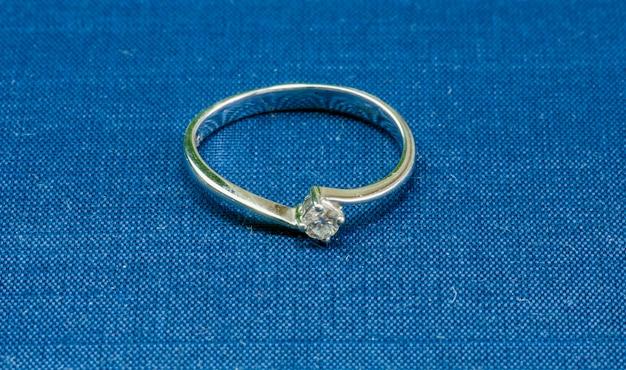 青いテーブルに宝石が付いたホワイトゴールドの指輪