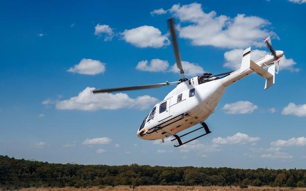 Белый вертолет взлетает с взлетно-посадочной полосы.