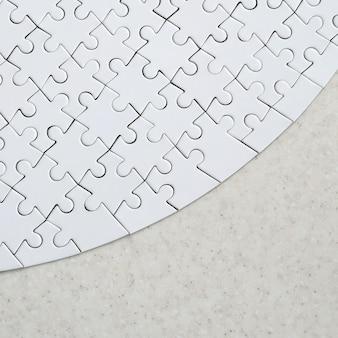 完全な形の白いジグソーパズルは処理された石の表面にあります。コピースペースを持つテクスチャ画像