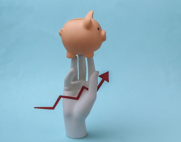 흰색 마네킹 손에는 위쪽을 가리키는 성장 화살표와 파란색 배경에 돼지 저금통이 있습니다. 금융, 경제 개념