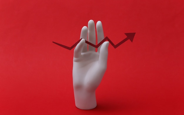 白いマネキンの手は、赤い背景の上向きの成長矢印を保持しています。ビジネス、経済の概念