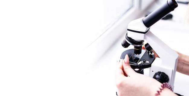 医学の科学研究所が分析するテーブル上の白い顕微鏡