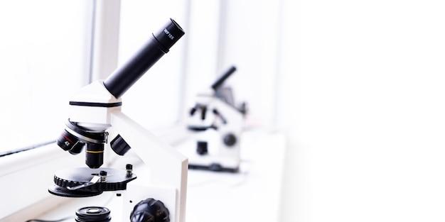 テーブルの上の白い顕微鏡医学の科学研究所が見通す