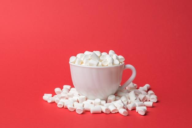 Белая кружка, наполненная зефиром. сладкое угощение.