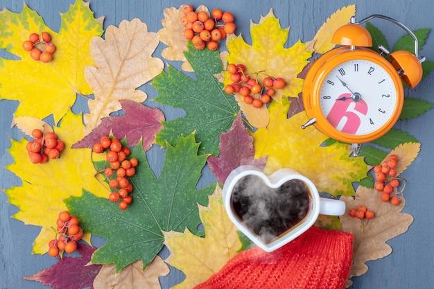 ハートの形をした白いマグカップに、蒸しコーヒーまたは紅茶、オレンジ色の目覚まし時計、秋の乾燥した色とりどりの葉に赤いスカーフ。朝食の時間。コーヒーを飲む時間。