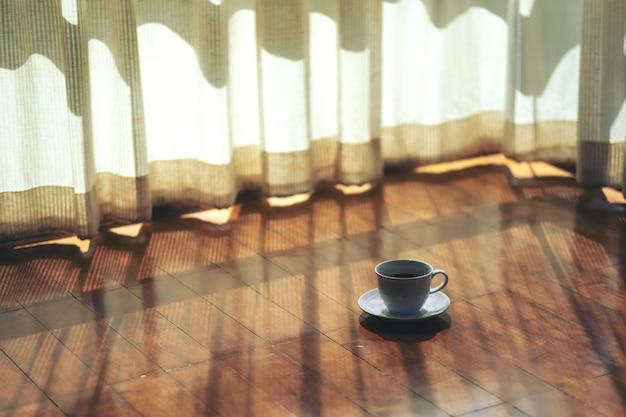 집의 커튼에 의해 나무 바닥에 뜨거운 커피의 흰색 머그잔