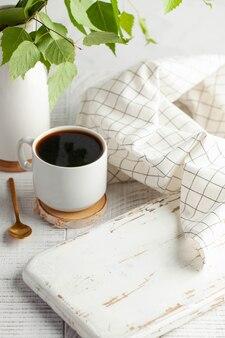 블랙 커피가 든 흰색 머그잔에는 녹색이 있는 가지가 제품을 삽입할 수 있는 빈 보드가 있습니다.