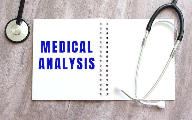 Medical analysis라는 단어가 있는 흰색 공책과 회색 나무 테이블에 청진기가 있습니다.