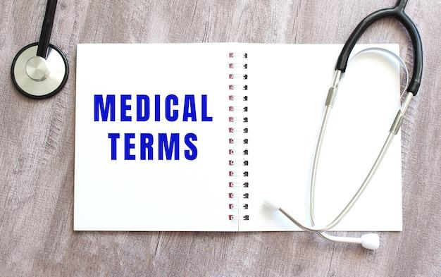 Medical terms라는 단어가 있는 흰색 공책과 회색 나무 테이블에 청진기가 있습니다.