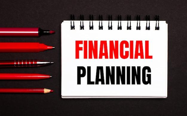 Белый блокнот с текстом «финансовое планирование», написанным на белом блокноте рядом с красными ручками, карандашами и маркерами на черном фоне.