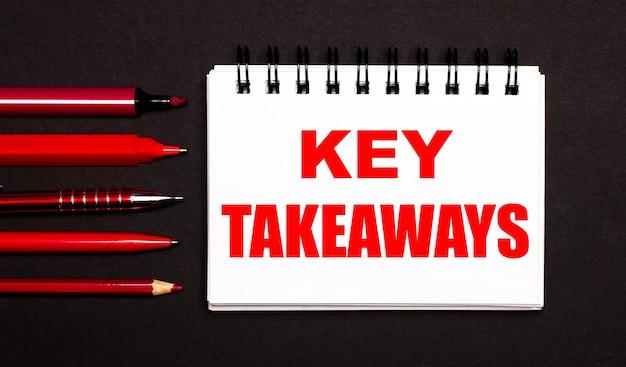 黒の背景に赤いペン、鉛筆、マーカーの横にある白いメモ帳に書かれた、「keytakeaways」というテキストが書かれた白いメモ帳。