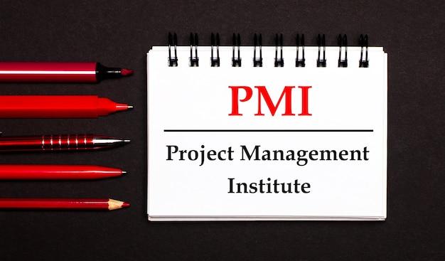 Белый блокнот с текстом pmi project management institute, написанным на белом блокноте рядом с красными ручками, карандашами и маркерами на черной поверхности.