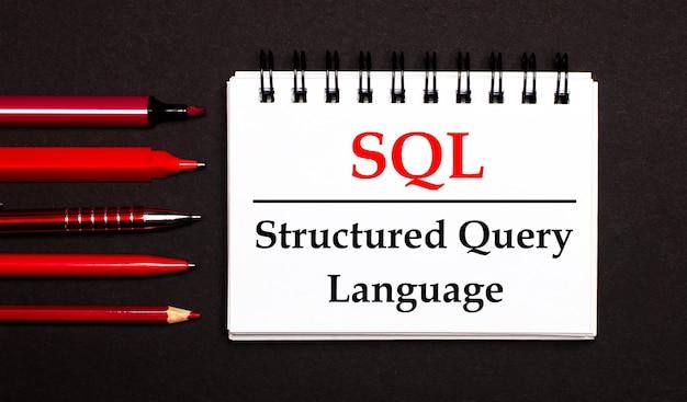 Белый блокнот с текстом sql structured query language, написанным на белом блокноте рядом с красными ручками, карандашами и маркерами на черном фоне.