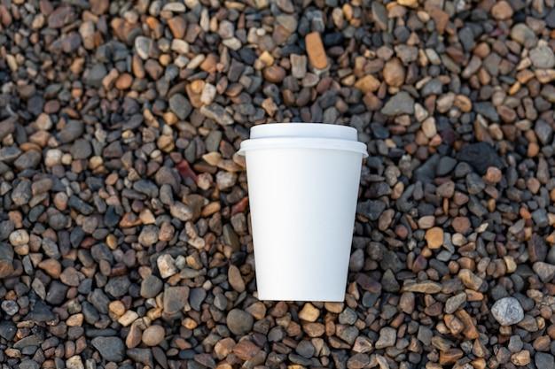 Белый бумажный стаканчик с кофе или чаем стоит на скалистом берегу. кружка горячего напитка на гальке. красивый скалистый фон. свободное место для копирования.