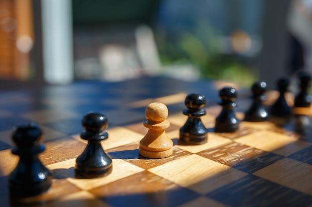 Белая пешка между черными шахматными фигурами на старой шахматной доске. концепция лидерства.