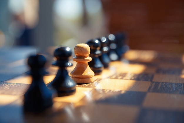 古いチェス盤の黒いチェスの駒の間にある白いポーン