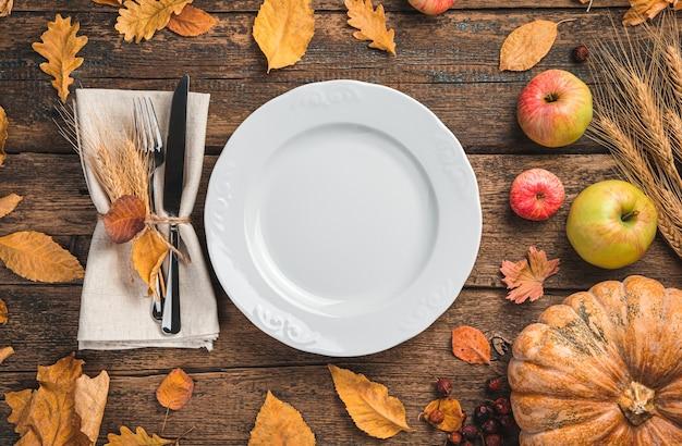 Белая тарелка столовых приборов с салфеткой на праздничном фоне с тыквенными яблоками и осенними листьями