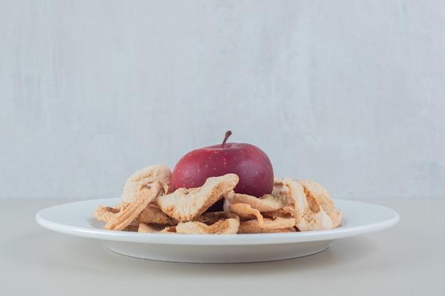 전체 사과와 말린 사과 과일의 전체 흰색 접시.